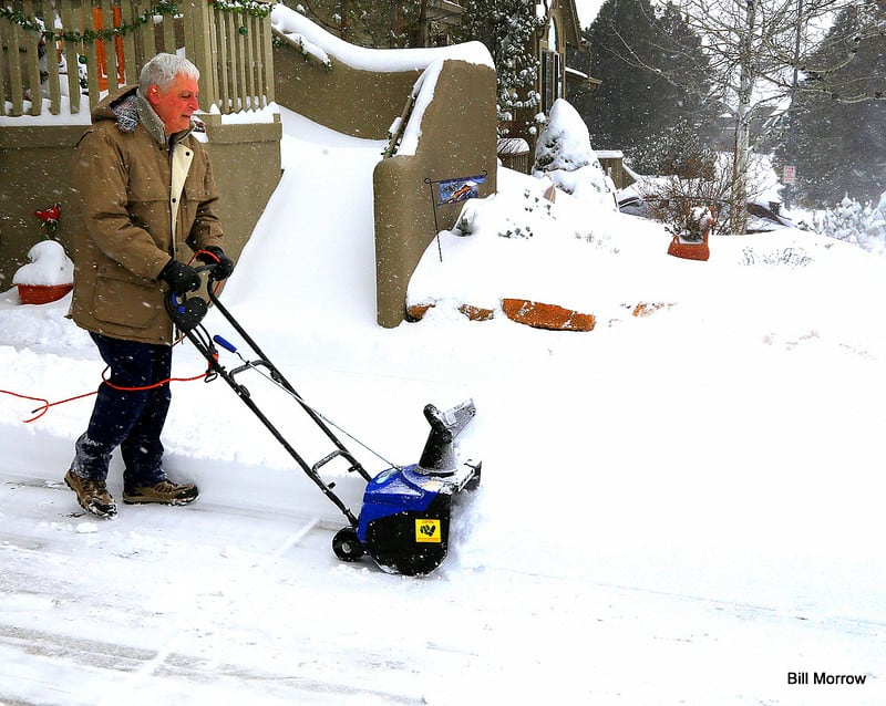 A man uses an electric snowblower for his pavement