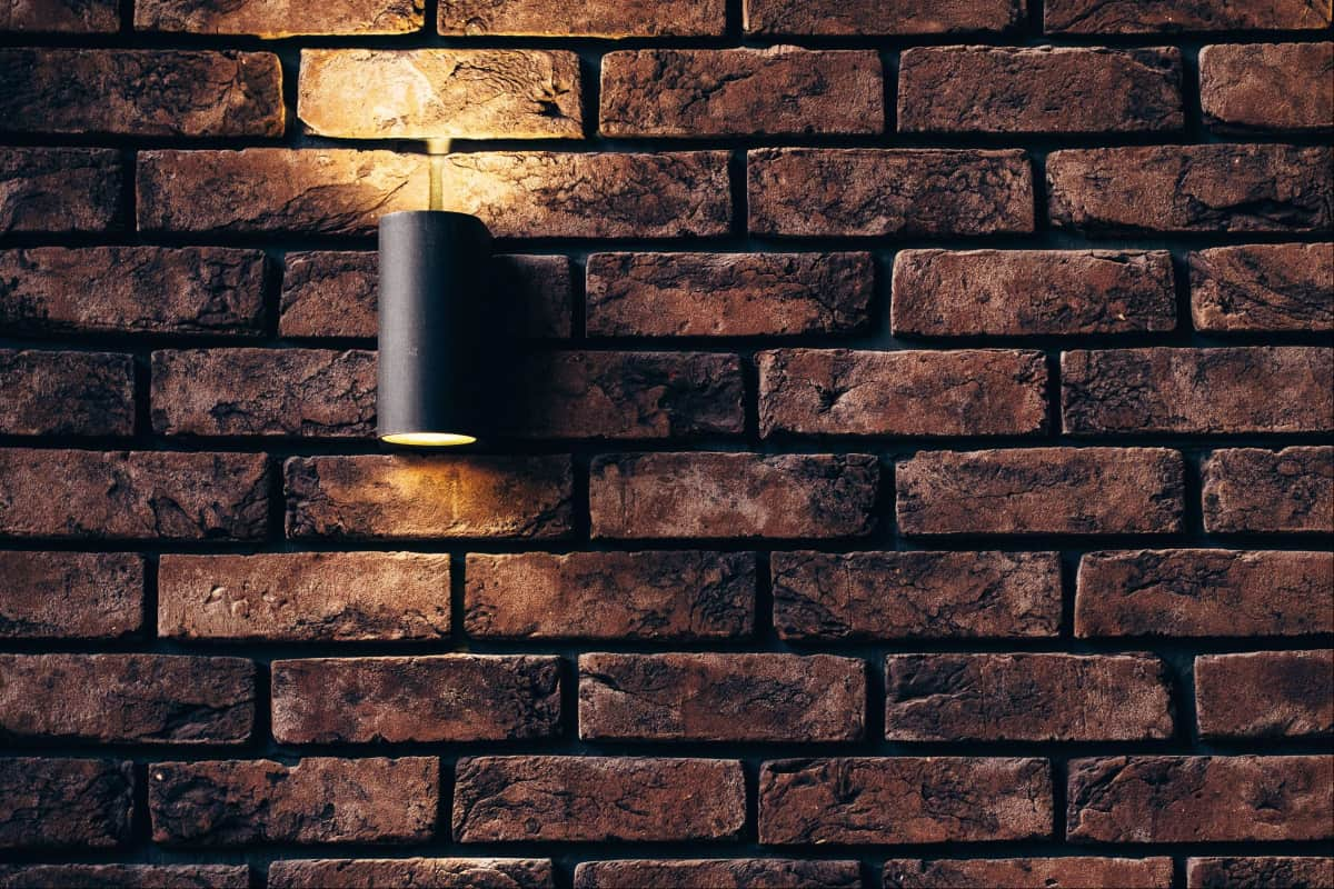 Designing a Guest Room Getting Tips From Coliving Spaces: Brick wall with a wall lamp