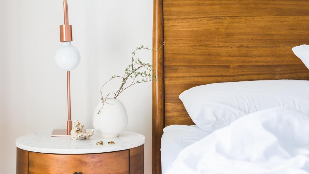 Designing a Guest Room Getting Tips From Coliving Spaces: Bed with white soft pillows and a side table