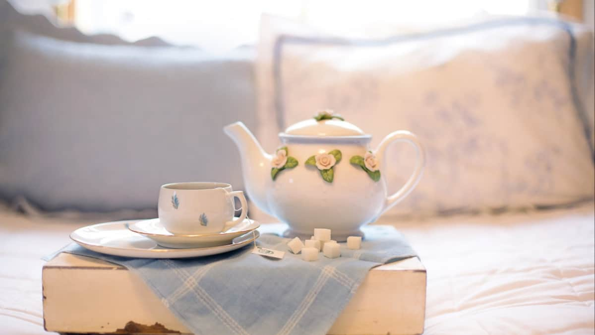 Designing a Guest Room Getting Tips From Coliving Spaces: Tea cup and pot on top of the bed