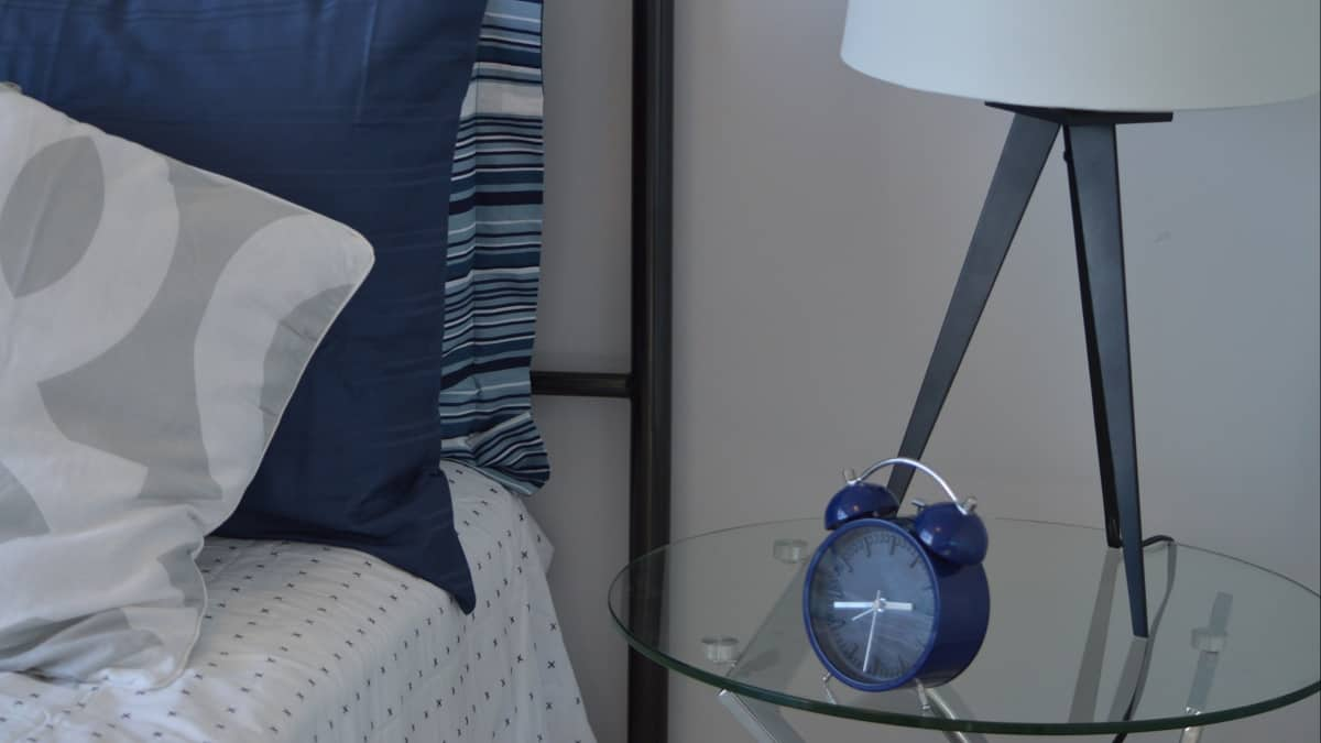 Designing a Guest Room Getting Tips From Coliving Spaces: Blue themed bed and pillows and a table side with a lamp and clock on top of it