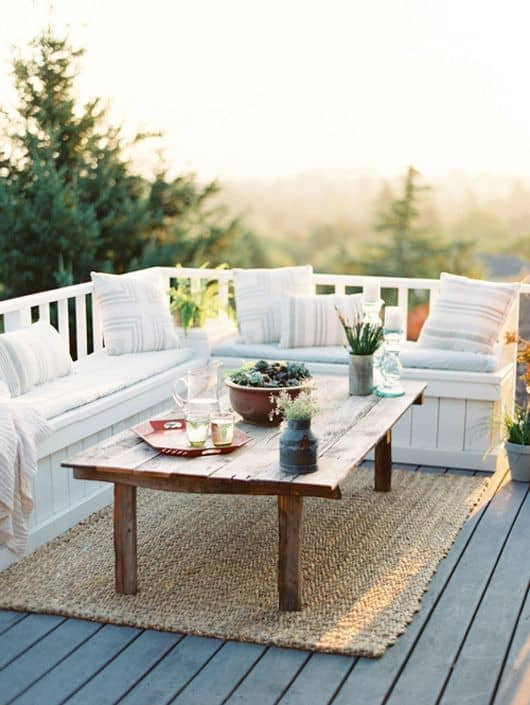 How To Keep Outdoor Rug From Blowing Away: Woven mats, white outdoor furniture and rustic table