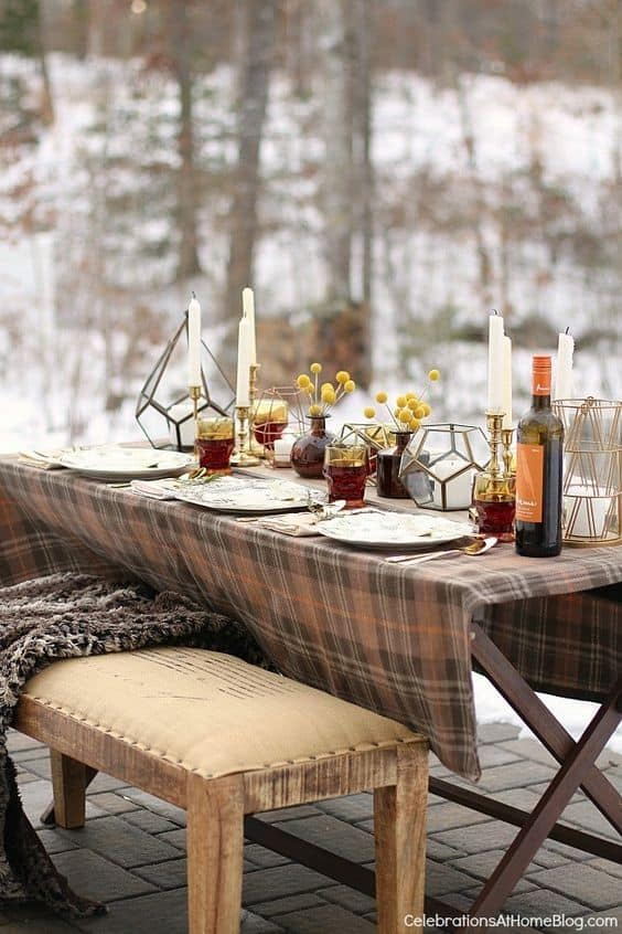 Outdoor winter party ideas: Winter outdoor table set-up with wine, plate candles, and utensils