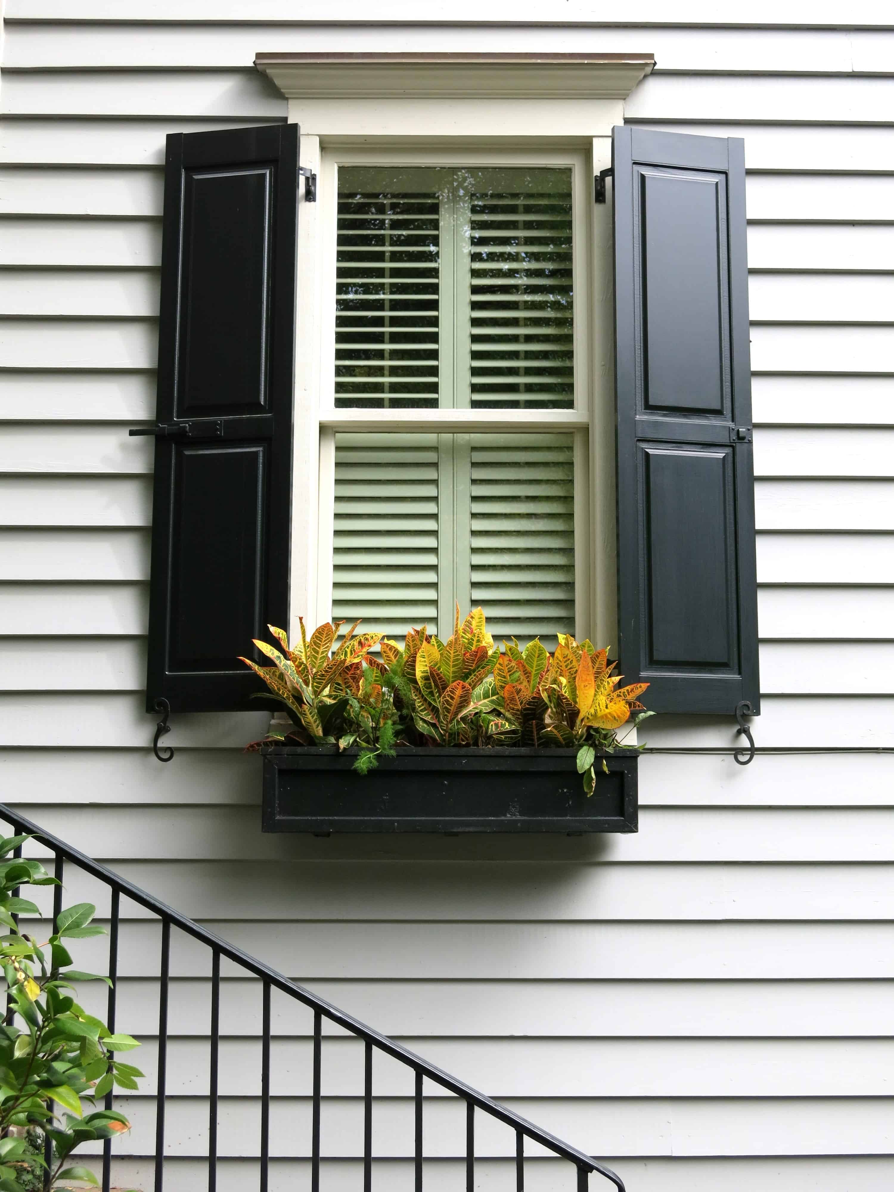 Curb appeal: Add flower boxes; opt for contrast colors to create a dramatic effect. Window box, black shutters, and wrought-iron railing, Wraggborough Lane, Charleston, SC