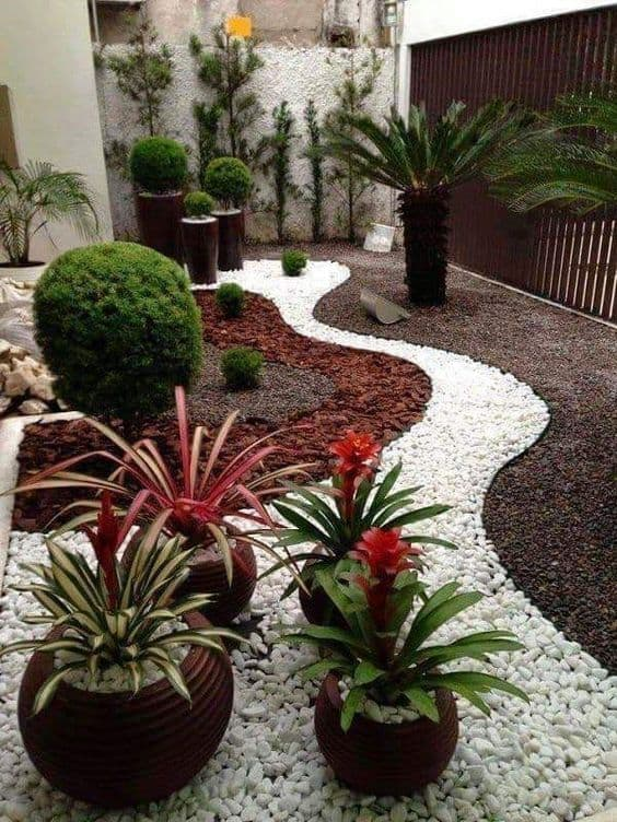 red plants, white rocks, and mulch