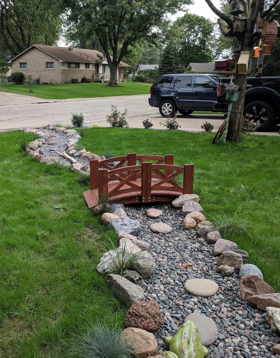 Dry river bed landscaping ideas: classic and elegant wooden bridge
