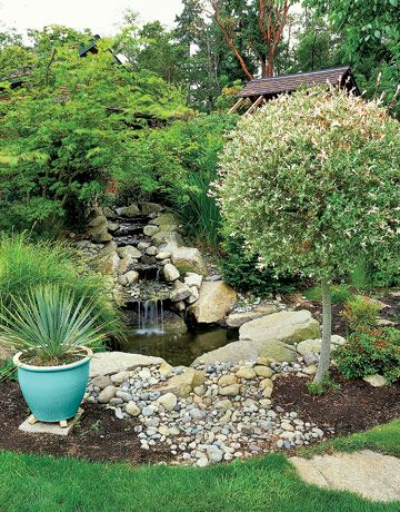 Landscaping ideas with mulch and rocks: rock-surrounded pond with mulch planting areas
