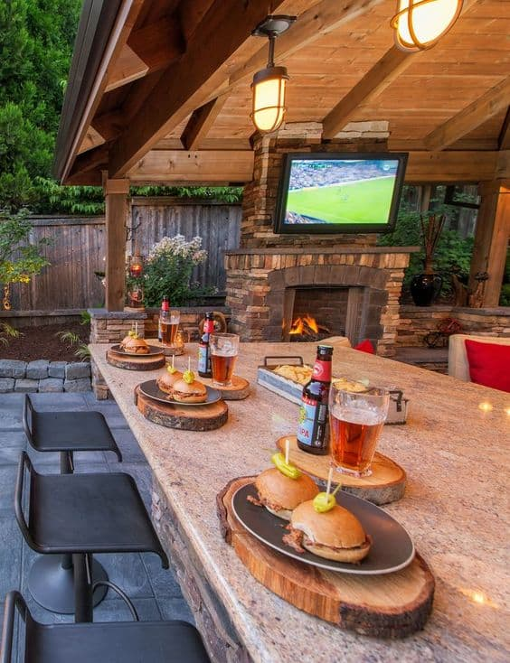 A pavilion with a bar, stools, and big screen tv.