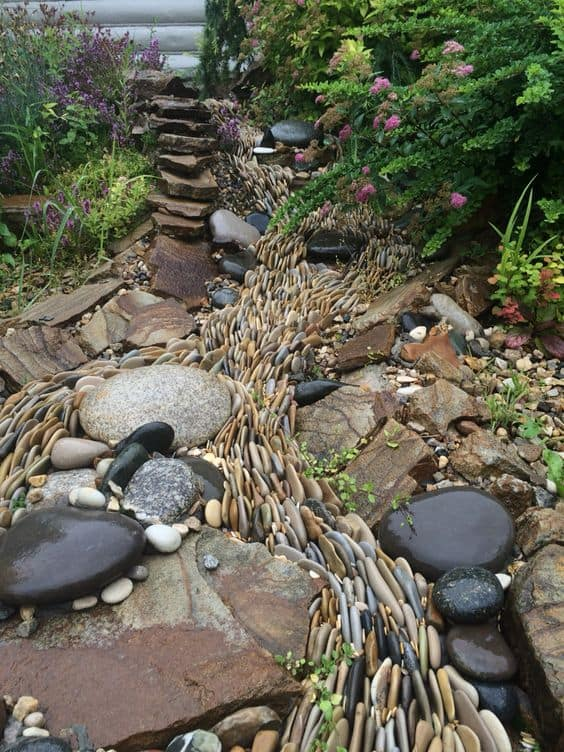 Dry river bed landscaping ideas: stones in different shades of beige, gray, black, and brown
