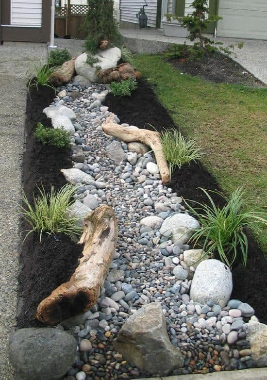 Dry river bed landscaping ideas: tree logs on the side of your dry river bed