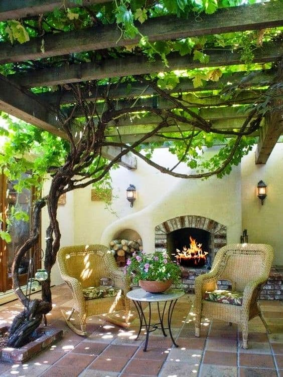 a tree creating a shade, furniture and a fireplace under the tree shade
