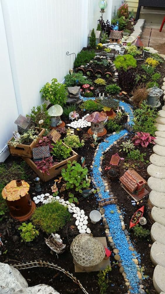 Dry river bed landscaping ideas: mini figurines and sculptures, like boats, houses, and benches