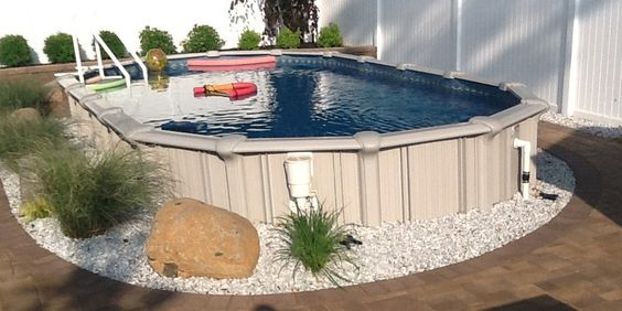 melania pool and its outside wall is decorated with white pebbles, rocks and plants