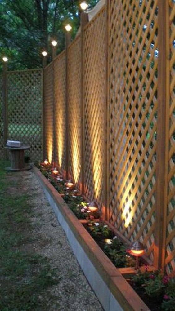 tall lattice wooden fence with lighting at the top of each support pole
