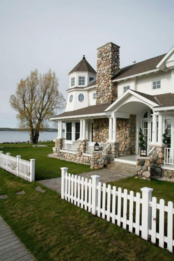 a big house near the river has a white picket