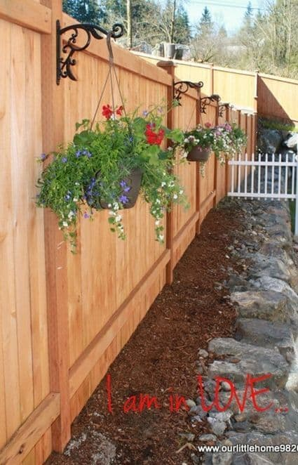 lighter shade of cherry wood fence with hanging flowering plants