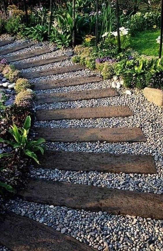 wooden pieces and pebbles for a curved walkway #walkway #Hardscaping #backyardLandscaping #backyardLandscapingIdeas #landscaping #cheapLandscapingIdeas #backyard #landscaping #curbAppeal  #rocks  #steppingStones #wood
