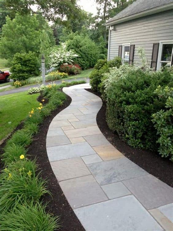 Custom curved walkway tile with mulch an plants on both side of the pathway #walkway #Hardscaping #backyardLandscaping #backyardLandscapingIdeas #landscaping #cheapLandscapingIdeas #backyard #landscaping #curbAppeal #mulch  #brickWalkway