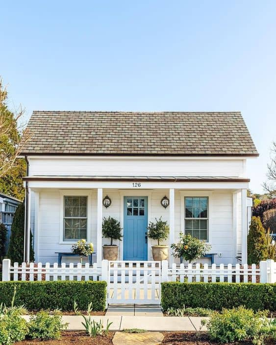 Bungalow house with white picket fence and gate