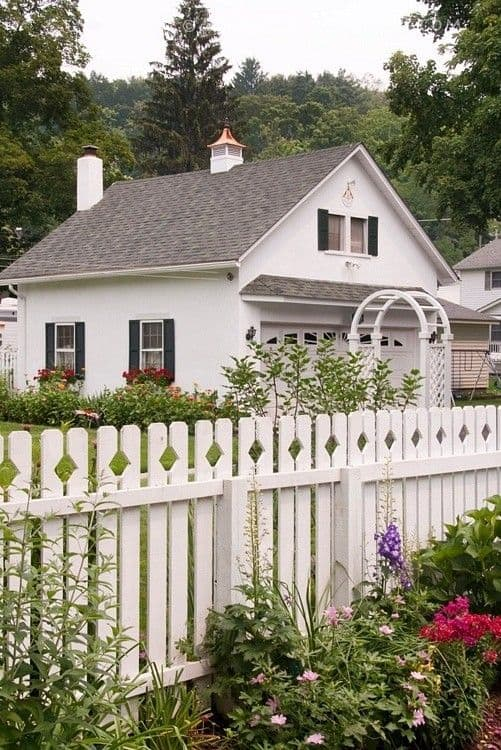 White house with a diamond shape pattern on the white picket fence and flowering plants