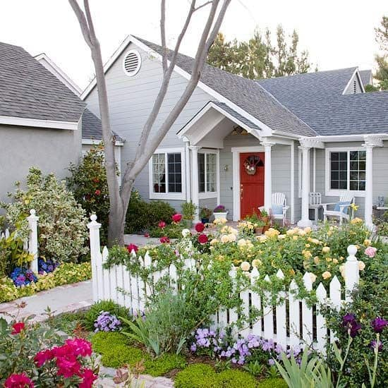 pointed wavy style picket fence for a home with beautiful flowering garden