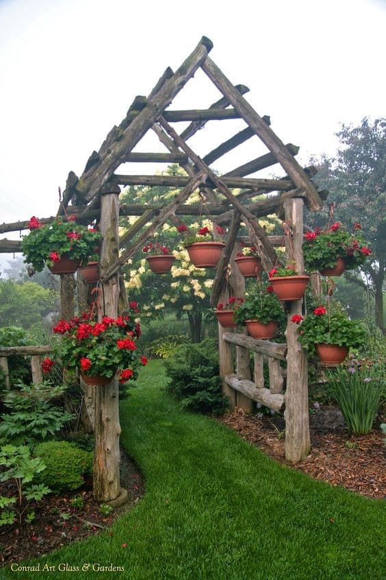 arbor with a countryside look made of big logs decorated with flower pot hanging on the side #arbor #backyardLandscaping #backyardLandscapingIdeas #landscaping #cheapLandscapingIdeas  #flowers #pergola #vines