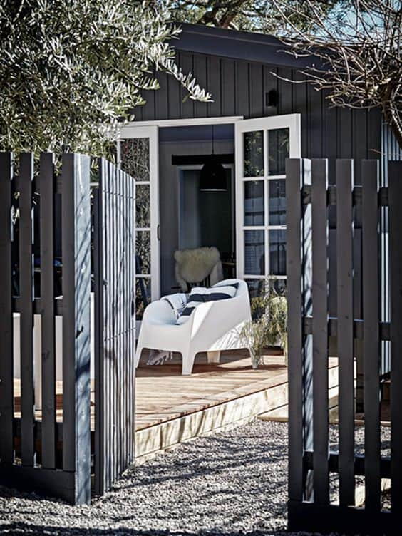 black house with black wood paneled gate and fence #fenceGate #fence #gardenfence #gardenfenceideas #privacyfenceideas #privacyfence #backyardLandscaping #backyardLandscapingIdeas #landscaping #gardenfence #gardenfenceideas #privacyfenceideas