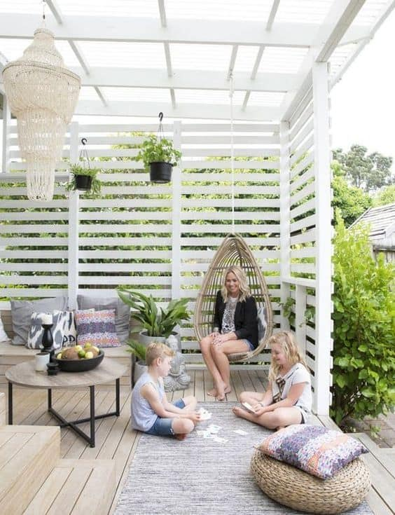 patio surrounded with a white fence  #patioideas #patiodeck #outdoorSpace #outdoordecor #patiodecor #patio #outdoorliving #outdoorFurniture#fence #privacyfence #pergola