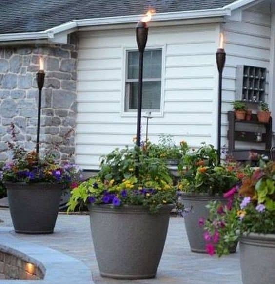floral/container/tiki torch combination  #flowers #containers #planters #gardenplanters #garden #backyardLandscaping #backyardLandscapingIdeas #landscaping #cheapLandscapingIdeas #backyard #landscaping #curbAppeal