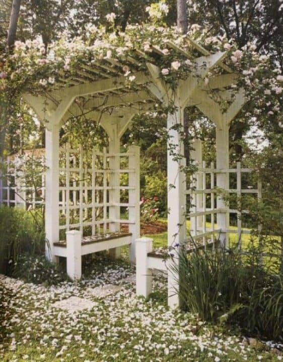 white arbor with bench seat #arbor #backyardLandscaping #backyardLandscapingIdeas #landscaping #cheapLandscapingIdeas  #flowers #pergola #vines