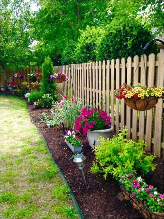 garden around the fence including hanging flowering plants  #flowers #containers #planters #gardenplanters #garden #backyardLandscaping #backyardLandscapingIdeas #landscaping #cheapLandscapingIdeas #backyard #landscaping #curbAppeal