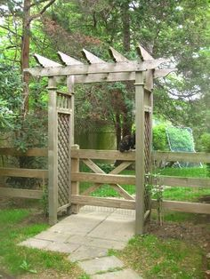 wood arbor with a gate that features a rustic look #arbor #backyardLandscaping #backyardLandscapingIdeas #landscaping #cheapLandscapingIdeas #pergola