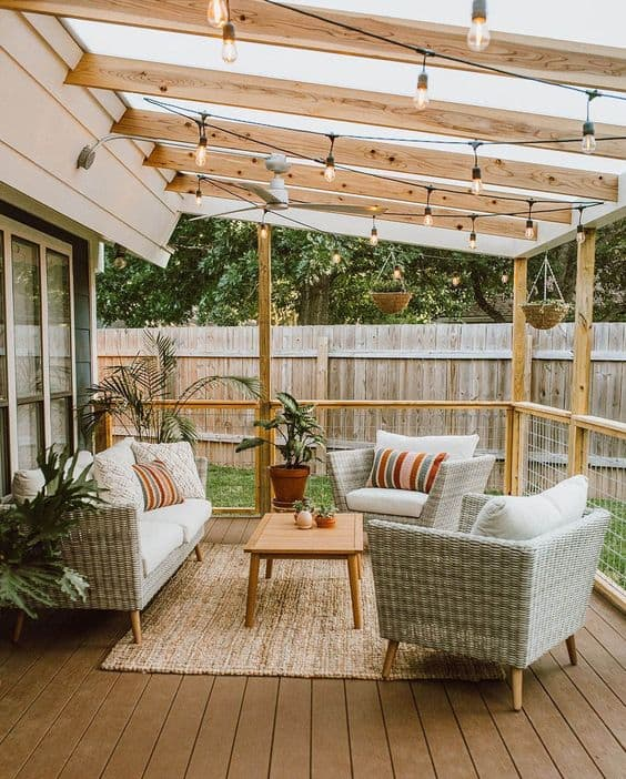 Patio decorated with plants and white shade furniture and surrounded with bare enclosure made of wood and metal  #patioideas #patiodeck #outdoorSpace #outdoordecor #patiodecor #patio #outdoorliving #outdoorFurniture#fence #privacyfence #pergola