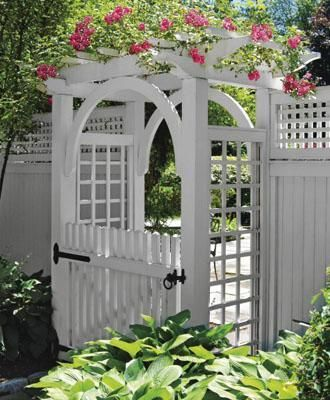 white arbor with a white pergola and fence, for a white fence #arbor #backyardLandscaping #backyardLandscapingIdeas #landscaping #cheapLandscapingIdeas  #flowers #pergola #vines