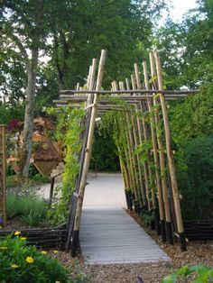 arbor made of tall logs  #flowers #pergola #vines  #arbor #backyardLandscaping #backyardLandscapingIdeas #landscaping #cheapLandscapingIdeas