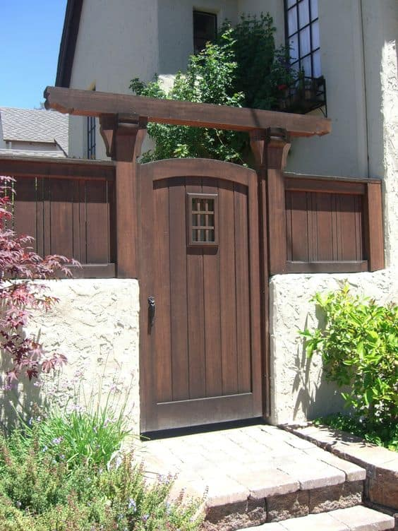 wooden gate in the middle of a brighter colored fence #fenceGate #fence #gardenfence #gardenfenceideas #privacyfenceideas #privacyfence #backyardLandscaping #backyardLandscapingIdeas #landscaping #gardenfence #gardenfenceideas #privacyfenceideas