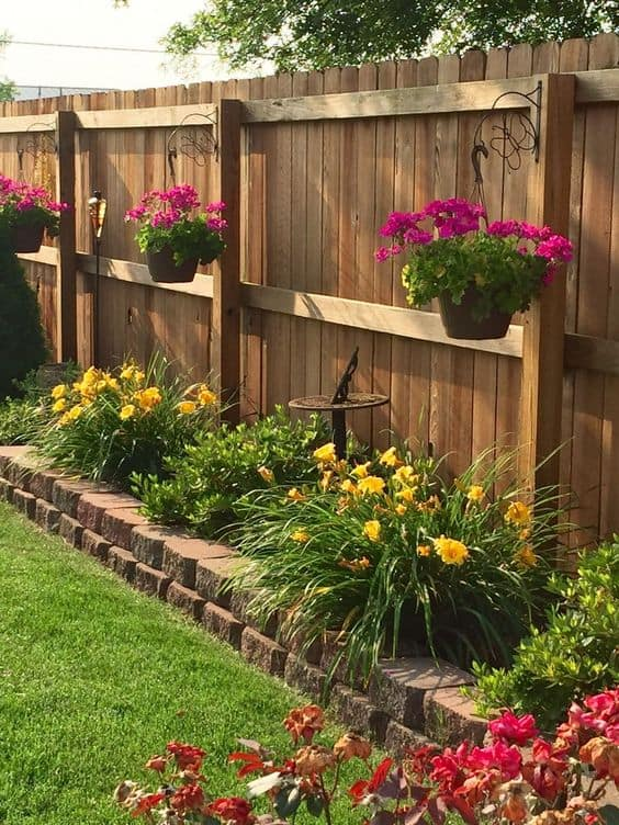 hanging potted plants, raised flower bed and a solid wooden fence  #flowers #containers #planters #gardenplanters #garden #backyardLandscaping #backyardLandscapingIdeas #landscaping #cheapLandscapingIdeas #backyard #landscaping #curbAppeal