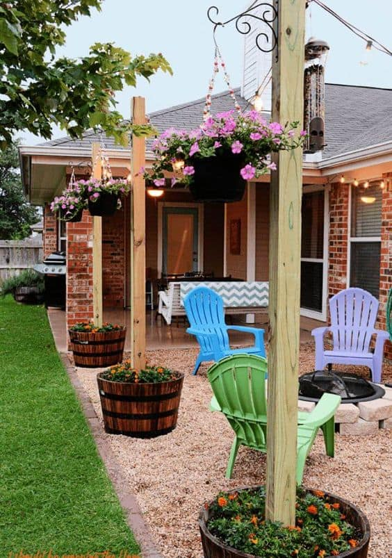 outdoor space, with firepit, hanging plants on a wood posts  #flowers #containers #planters #gardenplanters #garden #backyardLandscaping #backyardLandscapingIdeas #landscaping #cheapLandscapingIdeas #backyard #landscaping #curbAppeal