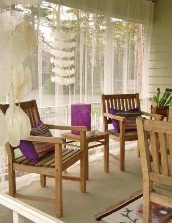 patio designed with wooden furniture, coral hanging decor, purple pillows and thin fabric curtains as an enclosure  #patioideas #patiodeck #outdoorSpace #outdoordecor #patiodecor #patio #outdoorliving #outdoorFurniture#outdoorCurtains #patioshade