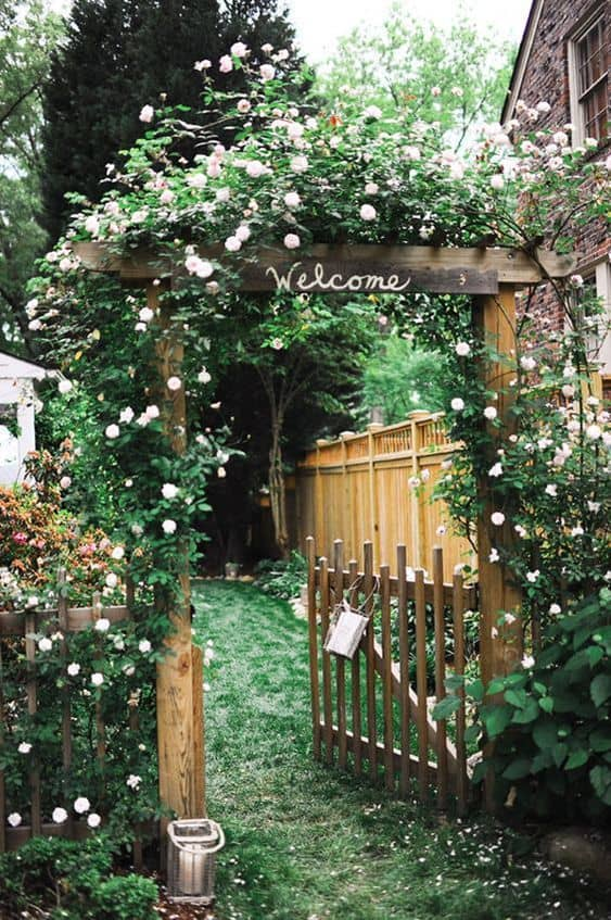 wood gate with a welcome sign is wrapped with flowering plants #fenceGate #fence #gardenfence #gardenfenceideas #privacyfenceideas #privacyfence #backyardLandscaping #backyardLandscapingIdeas #landscaping #gardenfence #gardenfenceideas #privacyfenceideas #flowers #arbor