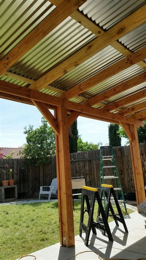 solid construction of a wooden pergola with a corrugated roof #pergola #backyardLandscaping #backyardLandscapingIdeas #landscaping #cheapLandscapingIdeas #landscape #pavilion #curbAppeal #outdoorliving #outdoorShade