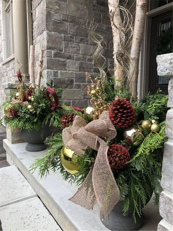 planters with gold ornaments that complement the red pine cones #porchIdeas #porch #winter #frontDoorDecor #homeDecor #patiodecor  #Planters