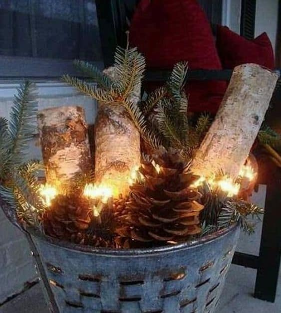 LED lighting for a planter wirh logs, pine cones and festive decor #porchIdeas #porch #winter #frontDoorDecor #homeDecor #patiodecor  #Planters