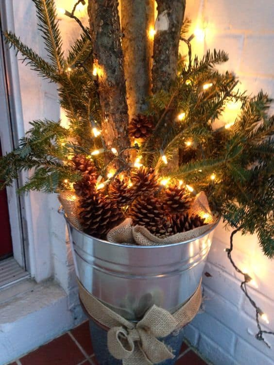 silvery planter combined with pine cones, pine fronds, and some logs #porchIdeas #porch #winter #frontDoorDecor #homeDecor #patiodecor  #Planters