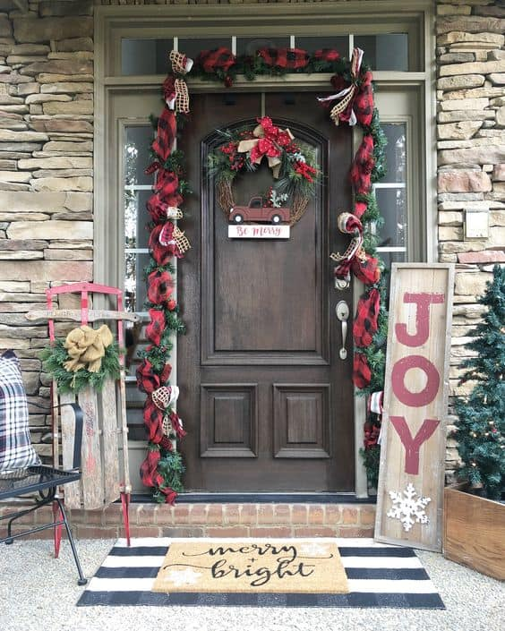 Decorate your front door with a garlands, wreaths and trees on the side #porchIdeas #porch #winter #frontDoorDecor #homeDecor #patiodecor