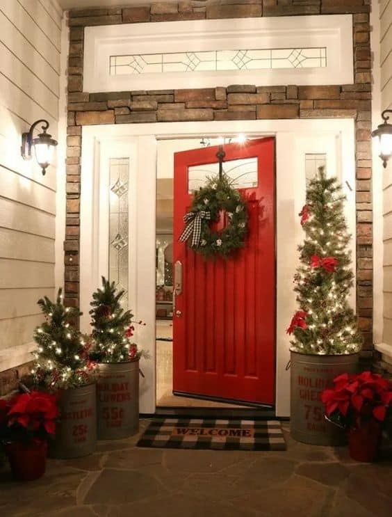 red door and trees of various sizes, which sit in big barrels  #porchIdeas #porch #winter #frontDoorDecor #homeDecor #patiodecor  #christmasTree