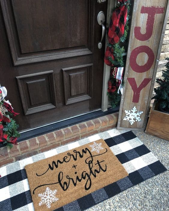 welcome mat feature a snowflake design, a sign board with the word joy and a door decorated with a garland #porchIdeas #porch #winter #frontDoorDecor #homeDecor #patiodecor