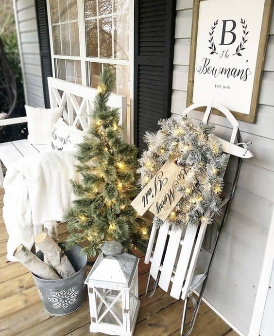winter white theme porch with white sled, lamp, christmas tree, white pillow and blanket  #porchIdeas #porch #winter #frontDoorDecor #homeDecor #patiodecor  #christmasTree