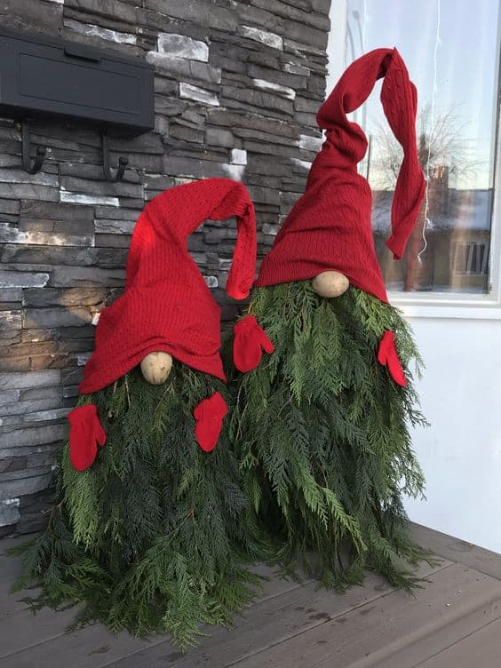 Chtristmas gnome made of a tree and decorated with a big hat and gloves #porchIdeas #porch #winter #frontDoorDecor #homeDecor #patiodecor  #christmasTree