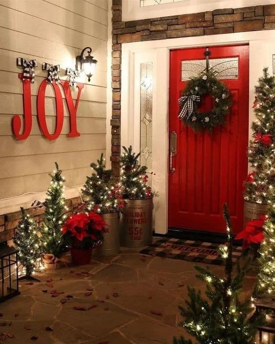 red door, small christmas trees with LED lights and a big joy sign #porchIdeas #porch #winter #frontDoorDecor #homeDecor #patiodecor  #christmasTree